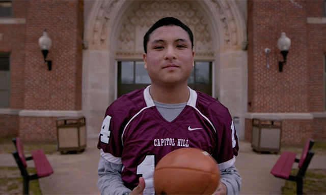 Capitol Hill High School Football Player in front of high school