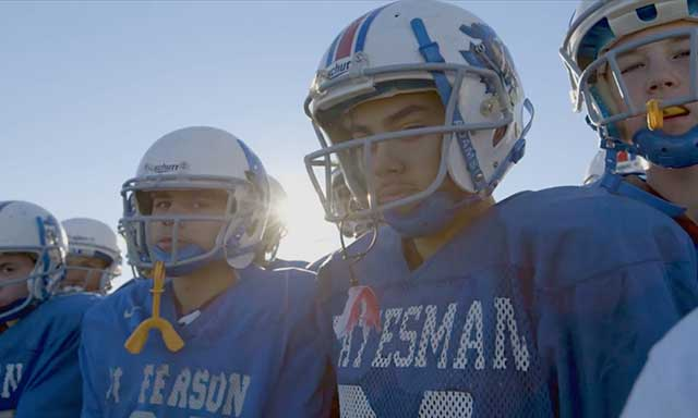 Middle school football players on a field revitalized by Fields & Futures