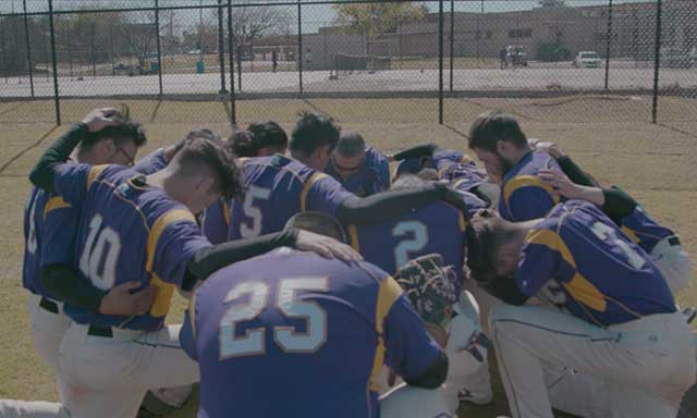 NW Classen High School baseball team huddling on field