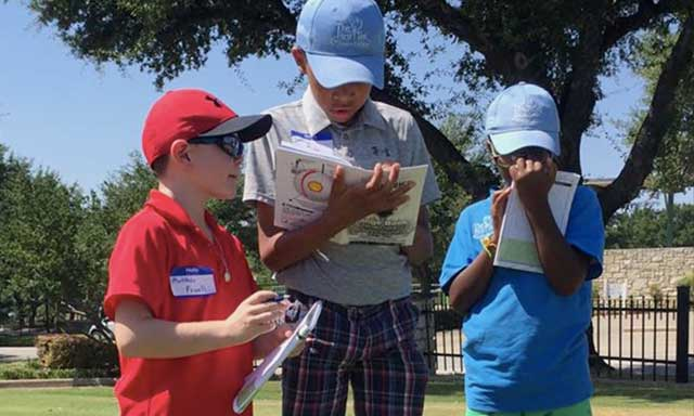 Youth golfers from The First Tee of Greater Dallas using their lesson books