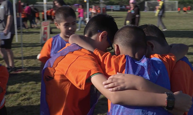i play! afterschool participants huddled up during a soccer game