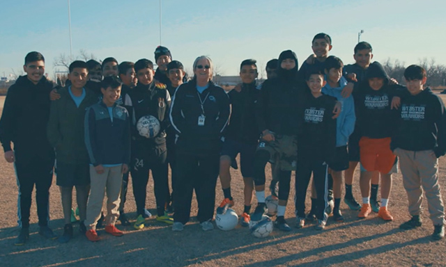 Katrinka Greear standing with the Webster Middle School soccer team on a field renovated by Fields & Futures in Oklahoma City