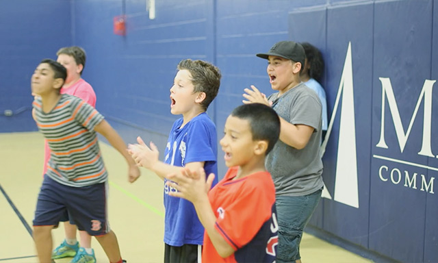 Boston youth cheering during a Doc Wayne Chalk Talk sports therapy program