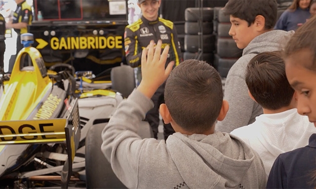 IndyCar Driver Zach Veach engaging with students during an Endeavor STEM program field trip at the race track.