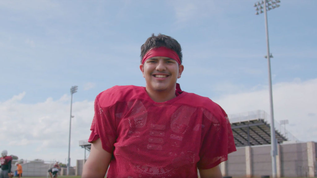 A Santa Fe South High School player is shown smiling during the Blended Brotherhood segment of Season 3, Show 3 of Power of Sports.