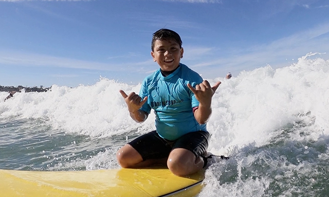 A kid seen surfing during the Power of Sports Community Spotlight – Urban Surf 4 Kids segment.