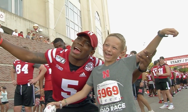 A Nebraska athlete poses with a child at a 5K fundraising event.