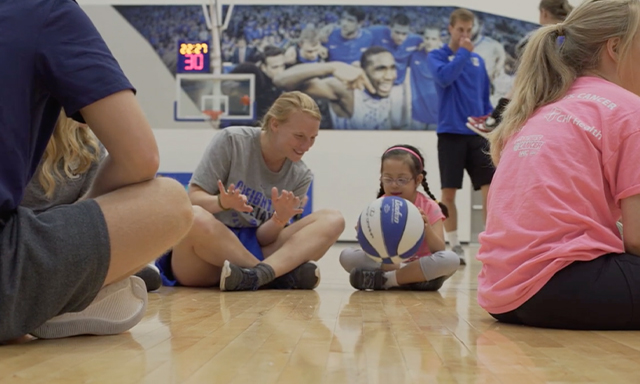 A Creighton basketball player teaches a student athlete how to dribble at a camp hosted in Nebraska.