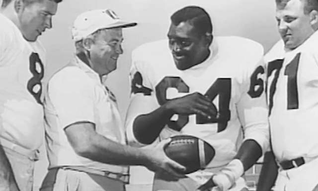 Coach Bob Devaney hands a ball to Bob Brown.